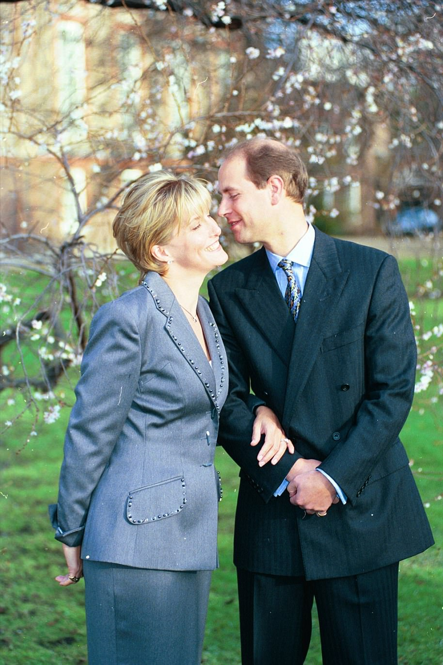 1999: Prince Edward and Sophie Rhys- Jones (Now the Countess of Wessex) pose for their engagement photo in the garden of St James' Palace. Sophie opted for a suit by Tomasz Starzewski. The photo sees the couple in a somewhat more intimate pose with Edward leaning in to place a kiss on Sophie's cheek