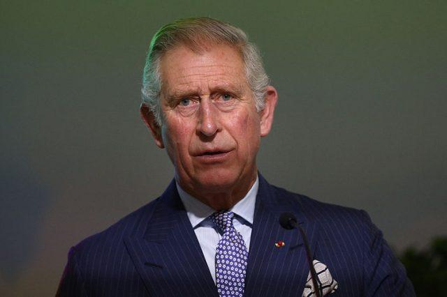 Prince Charles stands in front of a microphone wearing a blue suit and tie.