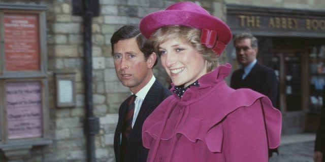 Prince Charles and Princess Diana walk side by side.
