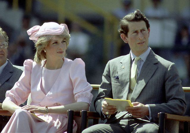 Prince Charles and Princess Diana sit together while outdoors at an event.