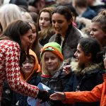Kate greets excited children who have gathered to meet her Photo (C) PA