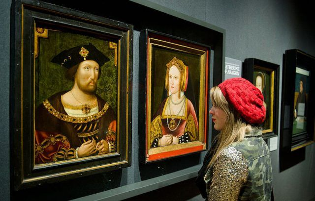 A woman observes painting of Henry VIII and Catherine of Aragon.