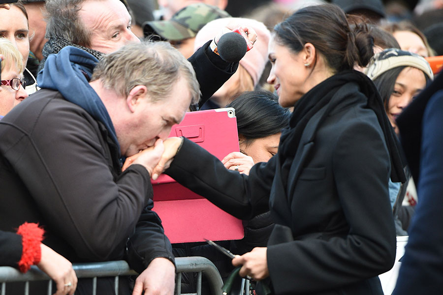 One enthusiastic royal fan kissed Meghan's hand as she greeted the crowds outside Cardiff castle on Thursday afternoon. Photo (C) GETTY IMAGES