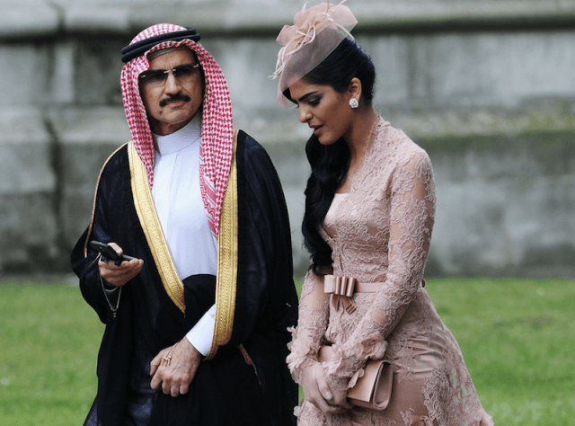 Prince Alwaleed bin Talal and Princess Ameerah Al-Taweel walking together outside.