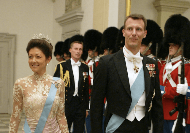 Prince Joachim of Denmark and Princess Alexandra walk past their security guards.