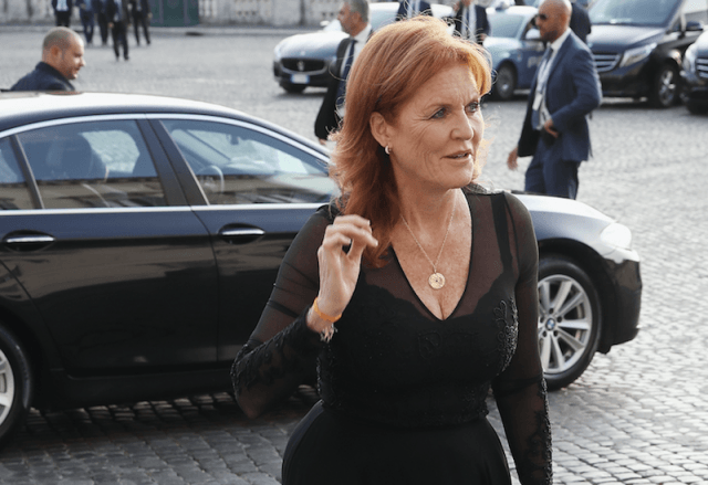 Sarah Ferguson walking past a black car.