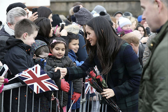 Meghan was given red roses by a young admirer Photo (C) PA