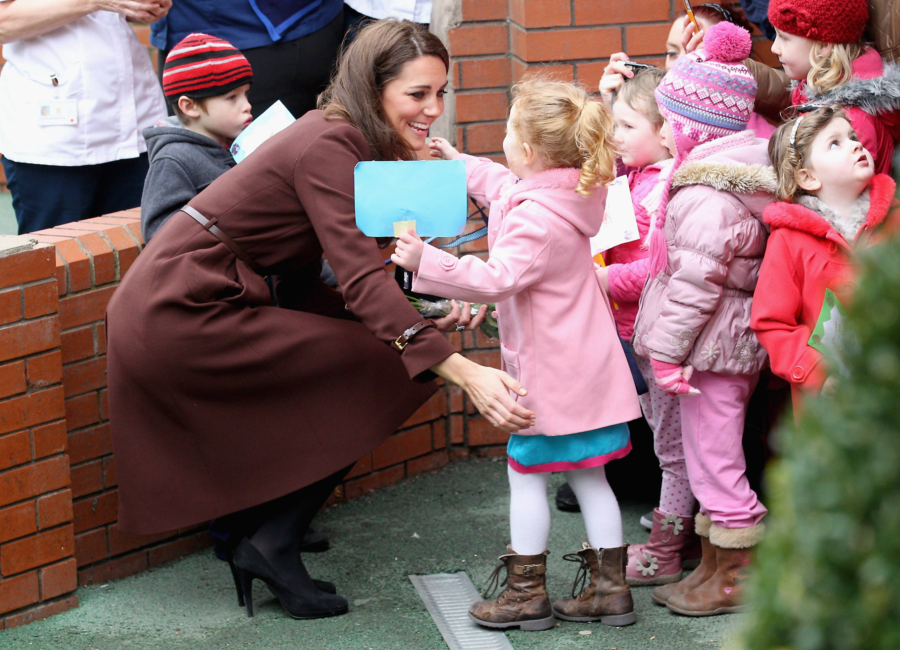 Catherine, Duchess of Cambridge hugs a young girl as she visits Alder Hey Children