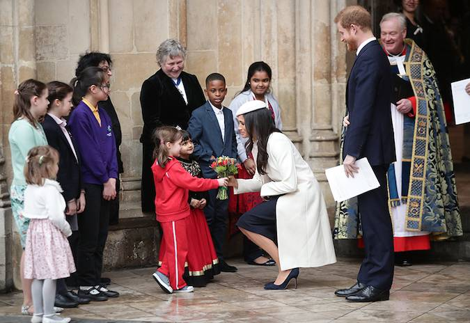 Meghan was later seen talking to children. One child even handed the future royal a lovely bouquet of flowers. Photo (C) PA