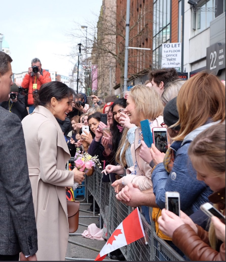 Ms. Markle receives a posy from a member of the public on Great Victoria Street in Belfast. Photo (C) TWITTER KENSINGTON PALACE