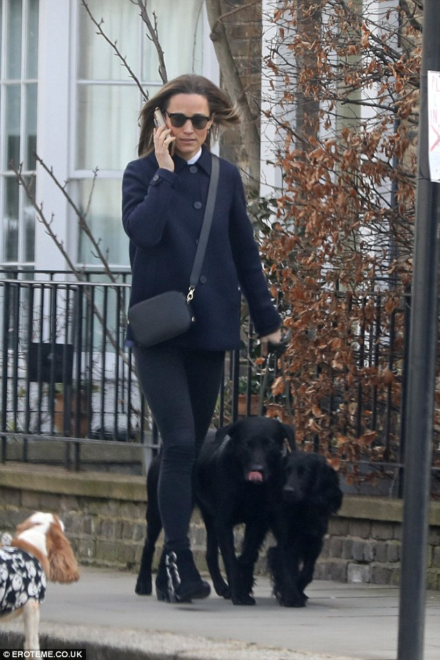 Pippa Middleton looked effortlessly chic in navy coat as she enjoyed a low-key walk with her Cocker Spaniel and black Labrador in London on Friday