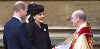A smiling look William dressed in his Sunday best looks on as Kate shakes the hand of the St Georges Chapel minister