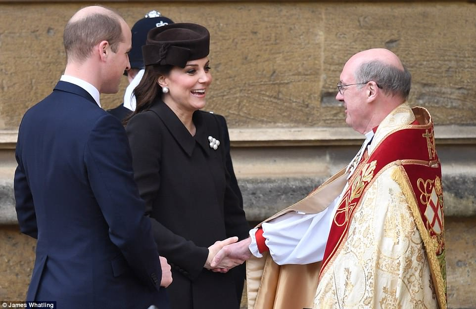 A smiling look William, dressed in his Sunday best, looks on as Kate shakes the hand of the St George's Chapel minister