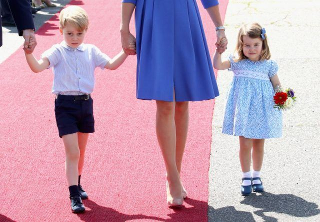 Prince George and Princess Charlotte of Cambridge holding Kate Middleton