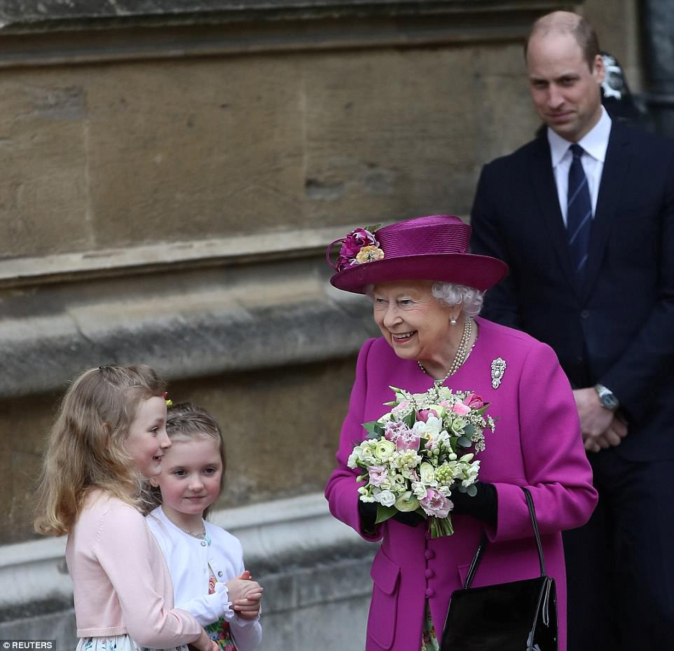 Prince William is seen smiling behind his grandmother as he watches her accept the pretty posy from the girls, both dressed in floral outfits