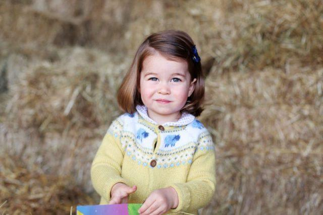 Princess Charlotte posing outdoors with her paintings.