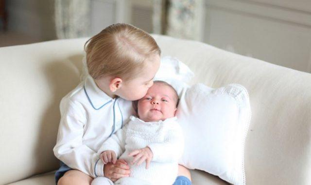 Prince George holding baby Princess Charlotte.