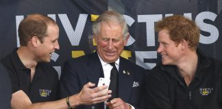 Prince William Duke of Cambridge Prince Charles Prince of Wales Prince Harry look at a mobile phone as they watch the athletics during the Invictus Games Photo C GETTY