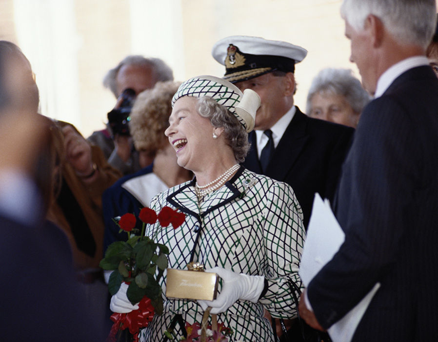 Queen Elizabeth II laughing while holding a small bouquet of flowers before boarding the Royal yacht Britannia Photo (C) GETTY