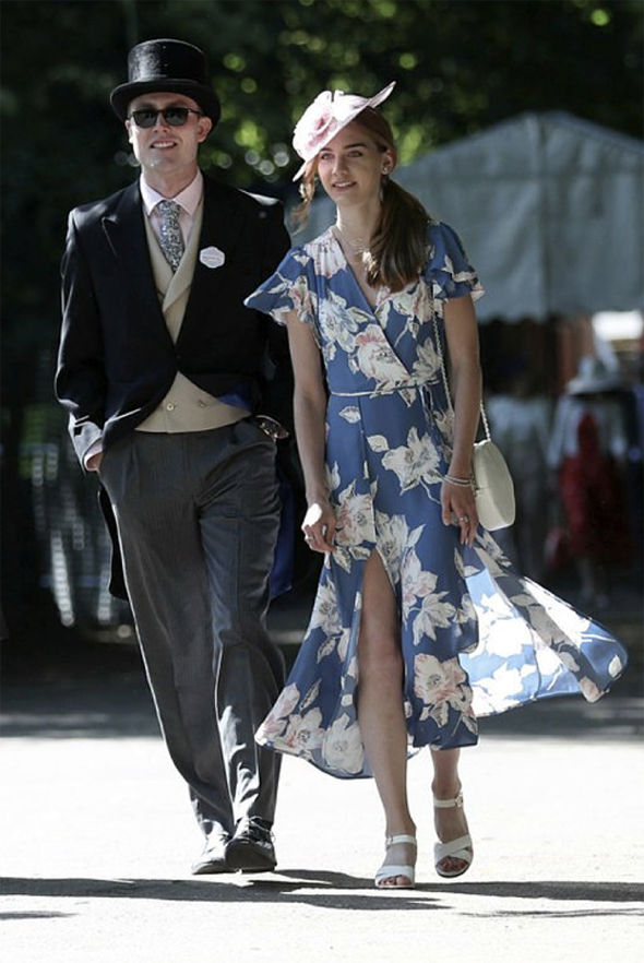 As racegoers arrived, a lady was spotted in a simple, elegant floral wrap dress with understated hat Photo (C) PA
