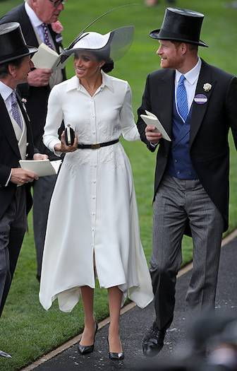 Meghan ticked all the boxes with her flowing white dress and her elegant hat. She accessorised with black heels and a small black clutch. Photo (C) Getty Images