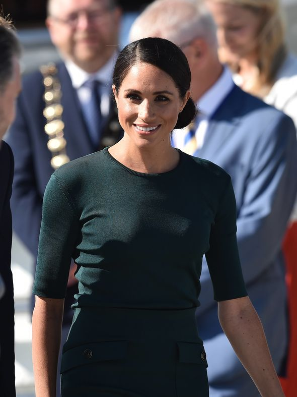 Meghan wears a green blouse and top