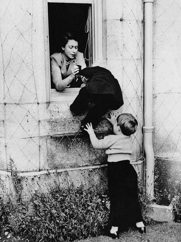 Elizabeth assists little Princess Anne through a castle window in 1953 (Image GETTY IMAGES)