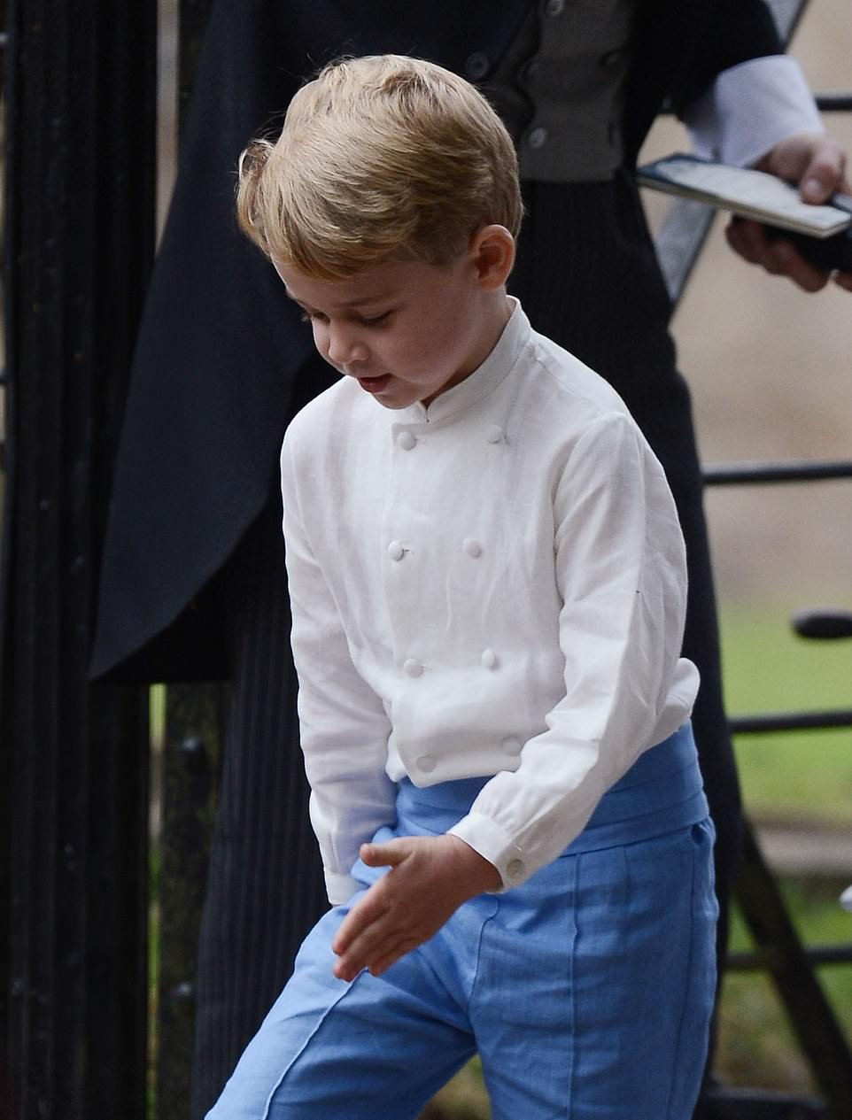 George wore a collarless white shirt, sky-blue knickerbockers, white stockings and white loafers