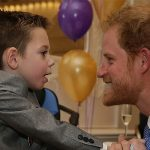 Prince Harry holds a child in a past visit to a WellChild facility (Image GETTY)