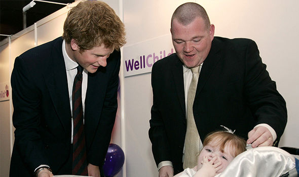 Prince Harry with a child being cared for by WellChild (Image GETTY)