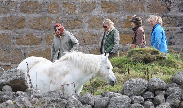The Queen inspects a white horse amidst the rugged terrain in the Scottish Highlands (Image Peter Jolly REX Shutterstock)
