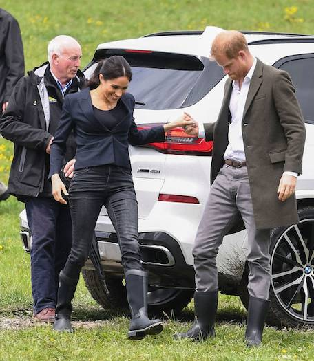 Adorable Prince Harry helps his wife avoid the mud as they arrive at Redvale North Shore to unveil the Queens Commonwealth Canopy in the area Photo C GETTY IMAGES