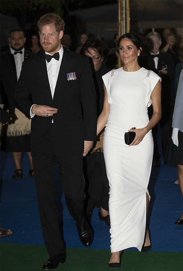 Meghan Markle dazzles in white as she clutches baby bump ...