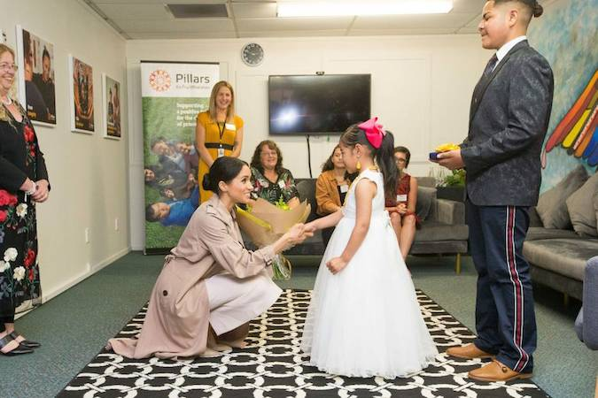 Meghan is greeted by a little girl at Pillars who had sweetly dressed up for the Duchess in her own princess dress Aw Photo C GETTY IMAGES