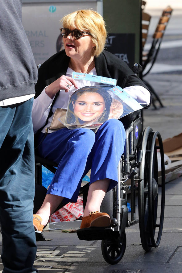 Samantha with a Meghan mask from a souvenir stand Image SPLASH NEWS