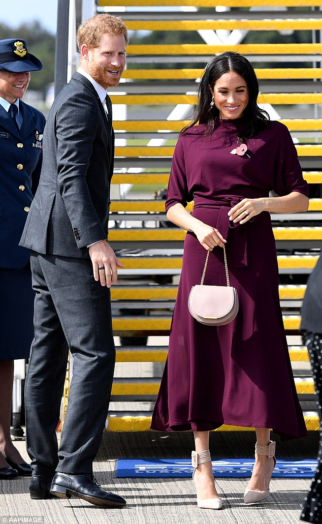 The Duchess of Sussex has stunned crowds in another fashion hit bidding farewell to Australia in a showstopping burgundy ensemble alongside Prince Harry