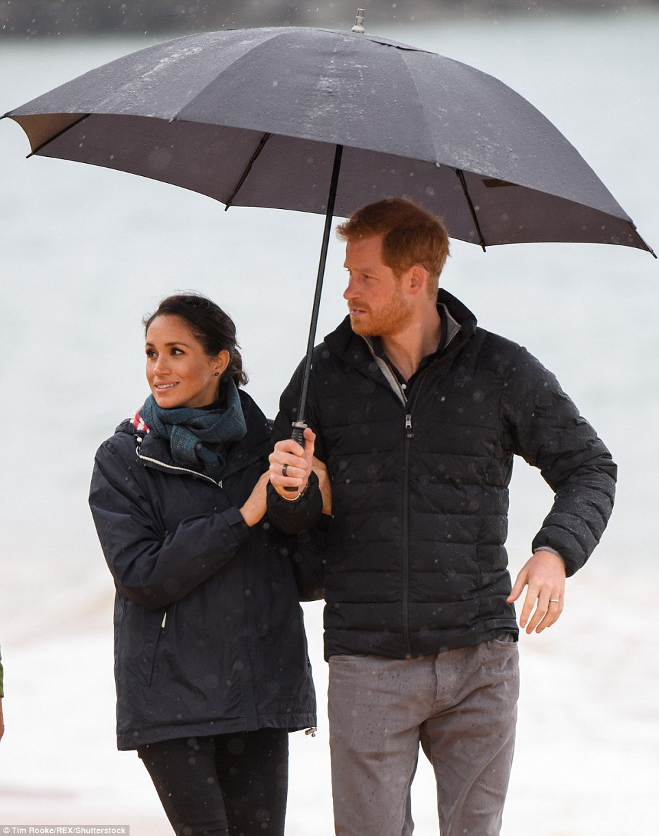 The couple stood under an umbrella as the rain came down but Harry was unfazed saying in a speech The rain is a blessing and a reminder of our connection to the land