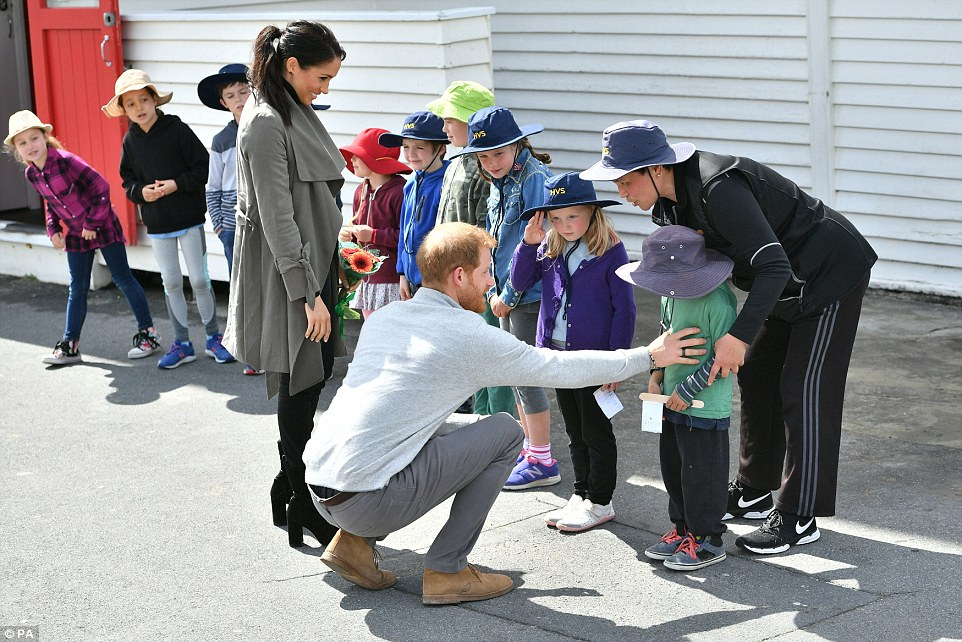 The pair were then joined by Prince Harry who mirrored Meghans maternal instincts by kneeling and attempting to speak with the little boy