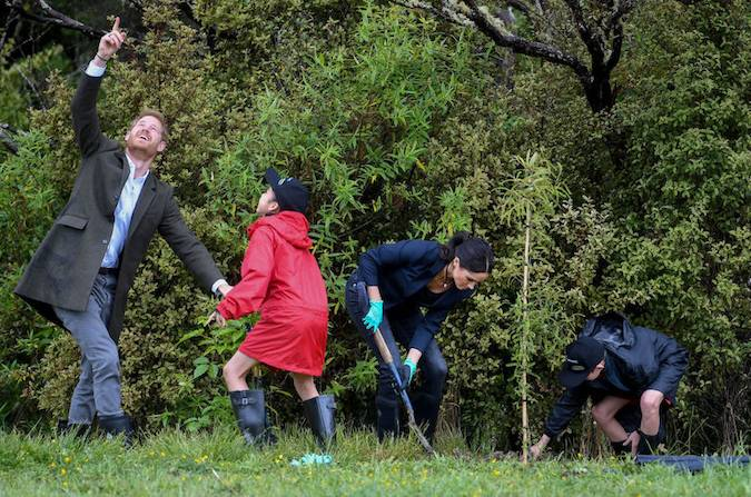 We love this shot of Prince Harry having fun with one youngster as he and Meghan helped them plant a tree at the site though Meghan seems to be doing most of the hard work Photo C GETTY