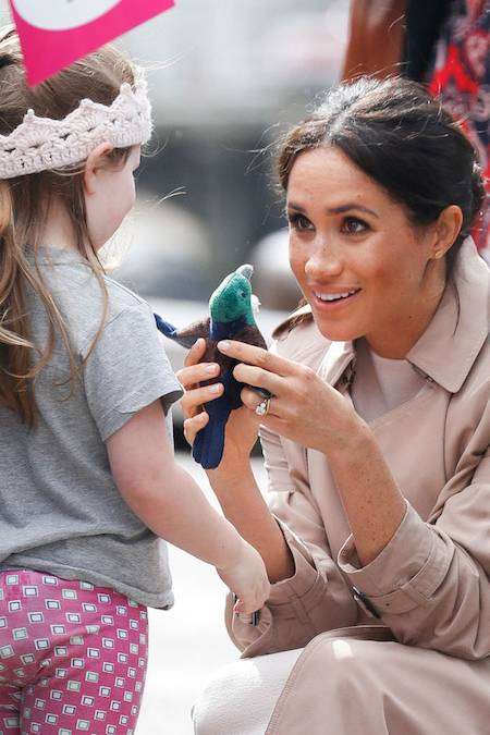 What an adorable snap of Meghan receiving a sweet baby gift from one little girl who wore a knitted crown during the walkabout Photo C GETTY