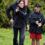 When it was her turn Meghan was a great sport as she tossed the pink polka dot welly into the air Photo C GETTY IMAGES