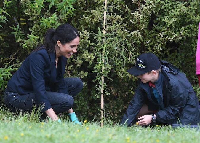 but it looks like she had just as much fun since she couldnt help but giggle as she helped plant the sapling Photo C GETTY IMAGES