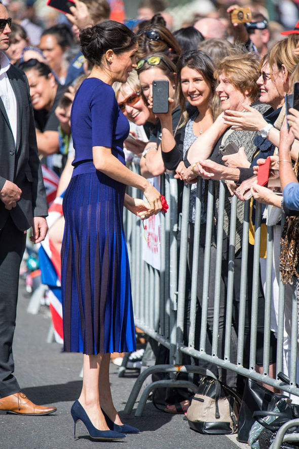 Meghan's legs appeared to be showing through her striped blue skirt Image GETTY
