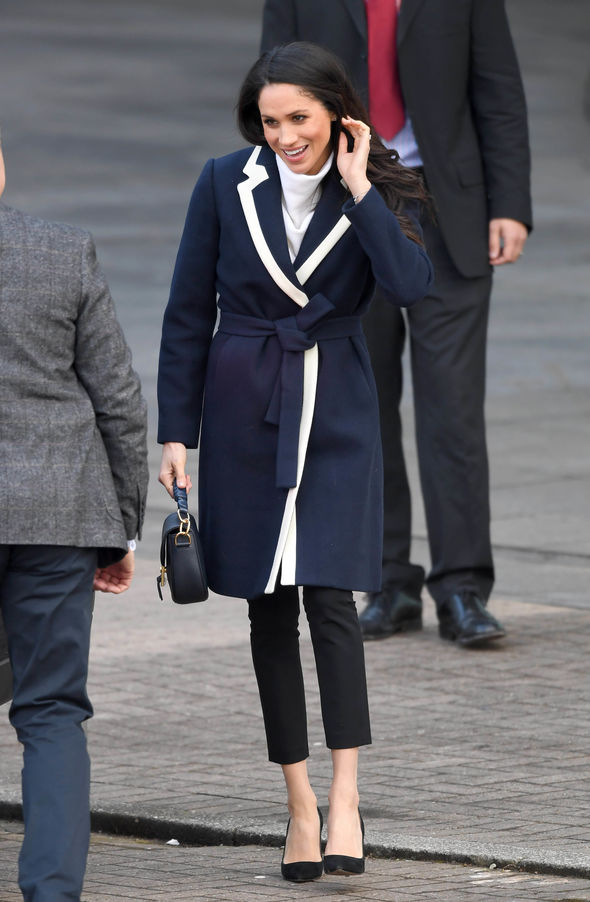 Meghan wore a long navy blue coat but missed the white cross sewn into the back Image GETTY
