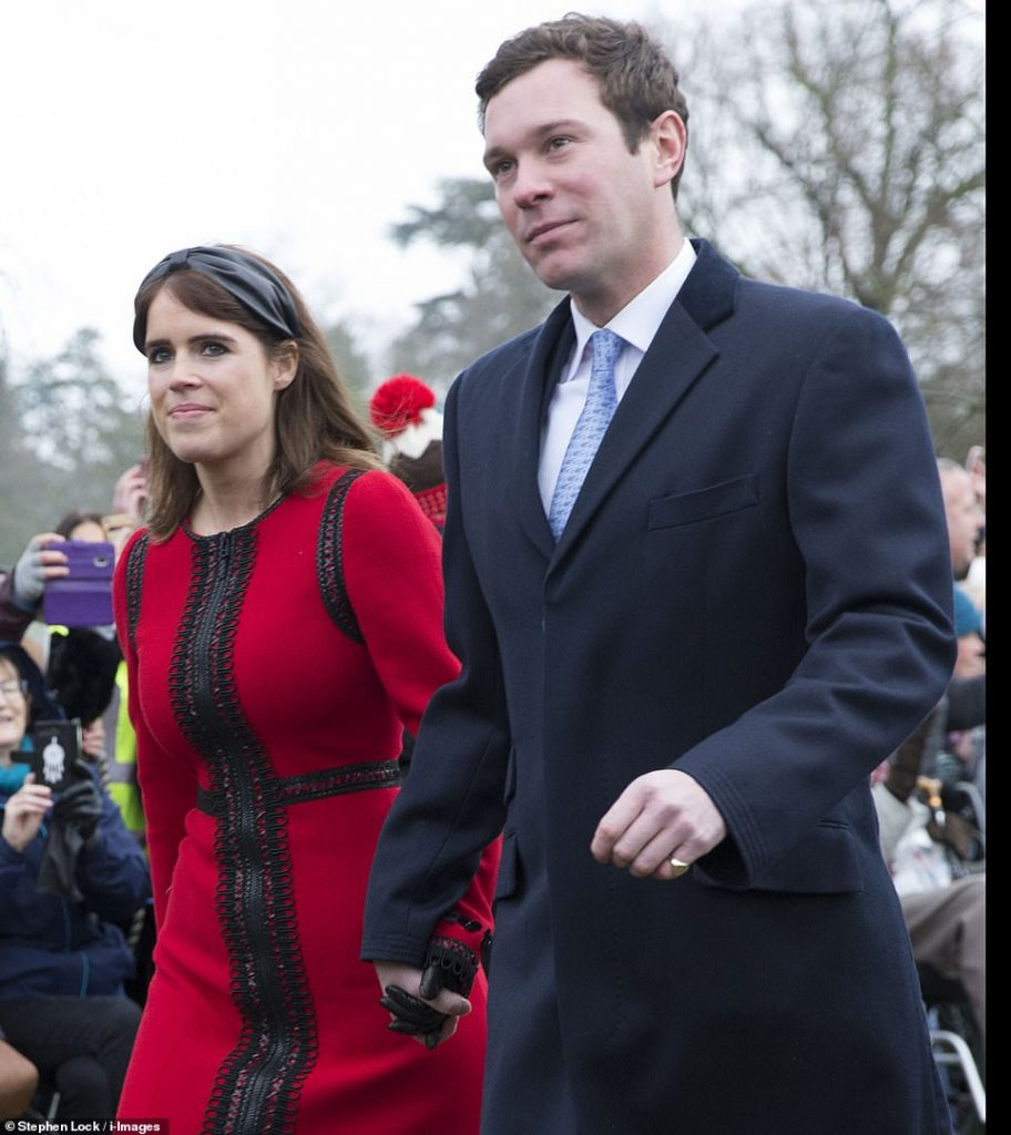 Eugenie opted for a more seasonal look in a red dress striped with an elaborate black pattern as she clutched her husbands hand