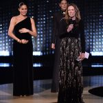 Even while the designer was accepting her award Meghan could be seen in the background holding her pregnant belly