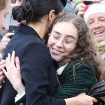 Meghan hugs a girl in the crowd