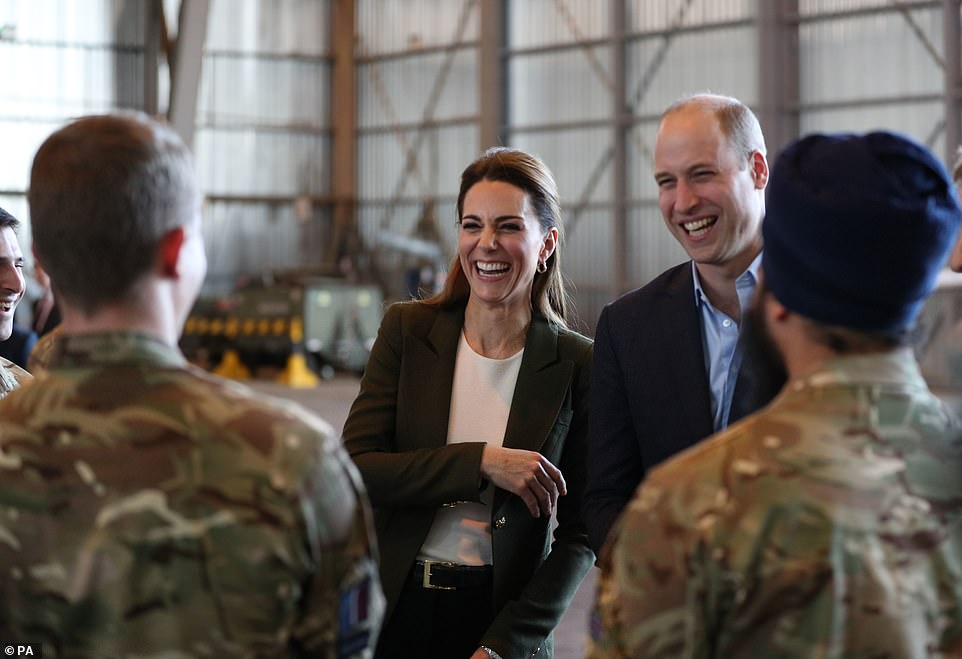 The duke and duchess of laugh as they meet members of 31 Squadron and other operational personnel in a hangar today