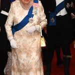 which she wore over a floor length gown as she arrived with the Queen and Prince Charles