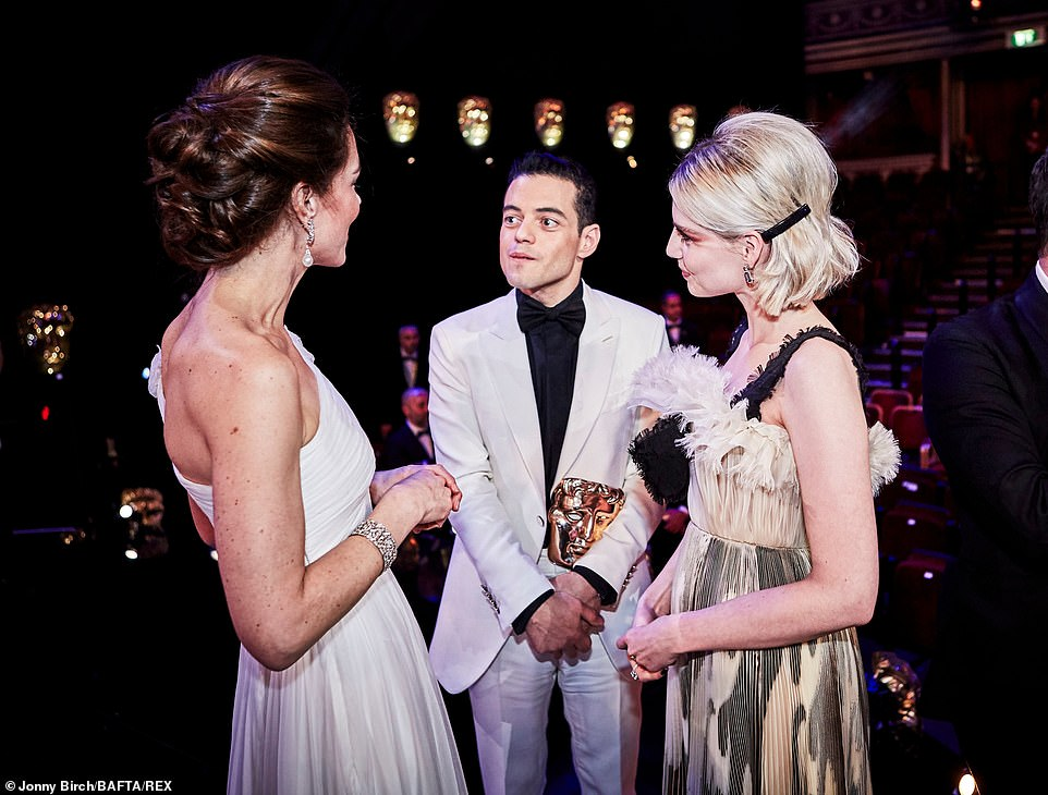 Kate chats to actors Rami Malek and Lucy Boynton The Duchess wore a dazzling white one shoulder gown by Brit designer Alexander McQueen